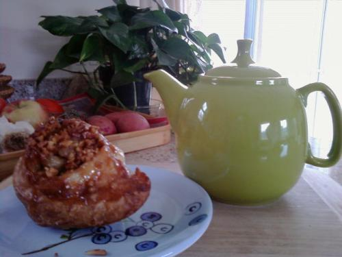 Sticky bun, teapot, vegetables and plant